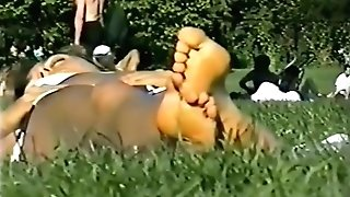 Lounging in the grass, fine view of feet and gams